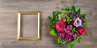 Golden picture frame and rose flowers. Vintage style mockup Royalty Free Stock Photography