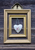 Golden picture frame on wooden wall and cloth heart Royalty Free Stock Photos