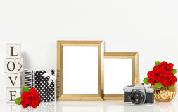 Golden picture frames, red rose flowers, vintage camera Stock Photos