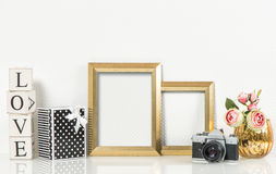 Golden picture frames, rose flowers and vintage camera. Product Royalty Free Stock Image