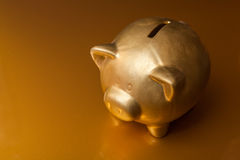 Golden Piggy Bank. On golden background Stock Photo