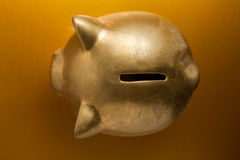 Golden Piggy Bank. On golden background Stock Photos