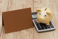 A golden piggy bank with card and calculator on wood background. With copy space for your message Royalty Free Stock Image