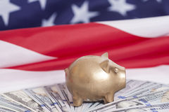 Golden Piggy Bank on Dollars with American Flag Royalty Free Stock Photos