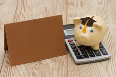 A golden piggy bank with grad cap, card and calculator on wood b. A golden with grad cap piggy bank, card and calculator on a wood background with copy space for Royalty Free Stock Photo