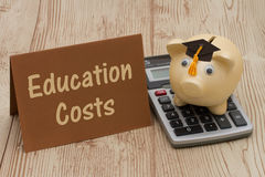 A golden piggy bank with grad cap, card and calculator on wood b. Education Costs, A golden with grad cap piggy bank, card and calculator on a wood background Royalty Free Stock Image