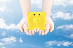 Golden Piggy Bank in hand. Sky background stock photos