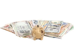 Golden piggy bank with International currencies Royalty Free Stock Photography