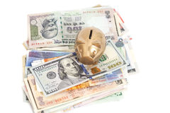 Golden piggy bank with International currencies Royalty Free Stock Photos