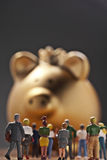 Golden Piggy Bank. Large group of modell figures in front of a monumental golden piggy bank with crown Royalty Free Stock Photography