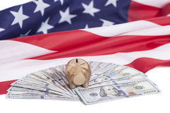 Golden Piggy Bank on One Hundred Dollars with American Flag Stock Photography