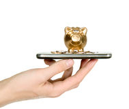 Golden piggy bank on top of mobile phone screen Stock Photo