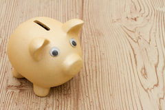 A golden piggy bank on wood background. A golden piggy bank on a wood background with copy space for your message Stock Photography