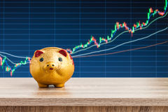 Golden piggy bank on wooden table with stock chart background,.  Royalty Free Stock Image