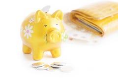 Golden piggybank with coins Stock Image