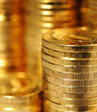 Golden piles of coins Stock Photos