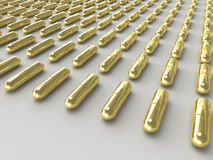 Golden pills Stock Photos