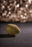 Golden pine cone ornament, bokeh background Royalty Free Stock Photo