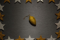 Golden pine cone ornament on slate with star frame Royalty Free Stock Photography
