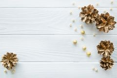 Golden pine cones with golden and beige beads on white wooden ta royalty free stock image