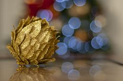 Golden pineapple on wooden table with christmas tree in the background stock image