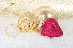 Golden and pink christmas balls in snow Stock Image