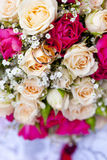 Golden wedding rings on wedding bouquet of pale pink and crimson or red roses Royalty Free Stock Photo