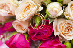 Golden wedding rings on wedding bouquet of pale pink and crimson or red roses. Golden plain wedding rings on wedding bouquet of pale pink and crimson or red Royalty Free Stock Image