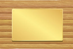 Golden plate. On wooden background Stock Photography