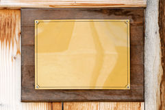 Golden plate. Blank golden name plate on wooden wall royalty free stock photography