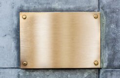 Golden plate or plaque made of bronze on wall Royalty Free Stock Photos