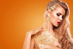 Golden Plated Woman`s Face. Art makeup. Stock Images