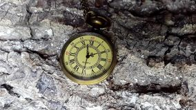 Golden Pocket Clock Ticking. This stock footage presents a close-up shot of a golden pocket clock ticking. The clock is lying on a rugged background, which looks stock video