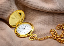 Golden pocket watch on fabric Royalty Free Stock Images