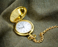 Golden pocket watch on fabric Stock Image
