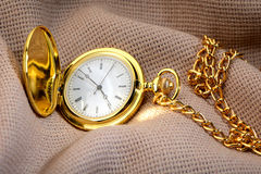Golden pocket watch on fabric Royalty Free Stock Photo
