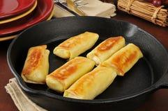Golden potato blintzes. In a cast iron skillet Royalty Free Stock Photos