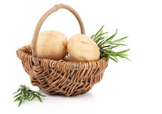 Golden Potatoes in wicker basket, with rosemary Stock Photo
