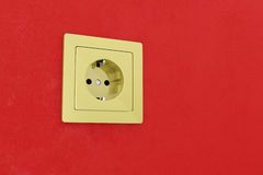 Golden power plug on red wall Royalty Free Stock Photography