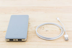 Golden powerbank and USB cable for smartphone. Stock Photography