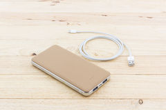 Golden powerbank and USB cable for smartphone. Royalty Free Stock Photo