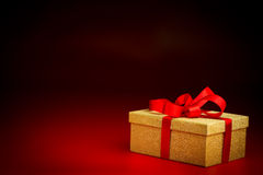 Golden Present Box With a Red Ribbon Royalty Free Stock Photography
