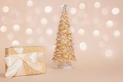 Golden present box with a silk bow against gold sparkling christmas pine tree on pastel background with beautiful stock photography