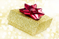 Golden present. On glittering background Stock Photography
