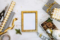 Golden ptoto frame, gift boxes, a crate full of pine cones and christmas toys and wrapping materials on a white wood old backgroun Stock Image