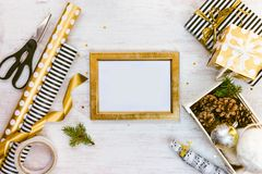 Golden ptoto frame, gift boxes, a crate full of pine cones and christmas toys and wrapping materials on a white wood old backgroun Royalty Free Stock Images