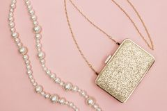Golden purse and pearl necklace on pink background. Beauty and fashion concept stock photo
