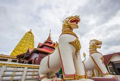 Golden Puttakaya chedipagoda with two giant Chinthe at the entrance,Sangkhlaburi district,Kanchanaburi,Thailand. Puttakaya chedi is a large golden chedi,located Royalty Free Stock Images