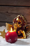 Golden putto with burning candle and star shaped christmas decorations on pile of snow Royalty Free Stock Photography