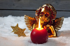 Golden putto with burning candle and star shaped christmas decorations on pile of snow Royalty Free Stock Photos